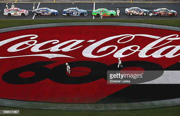 Officials run to clean up cables from an aerial Fox Sports camera on the front stretch during a red flag in the NASCAR Sprint Cup Series CocaCola 600...
