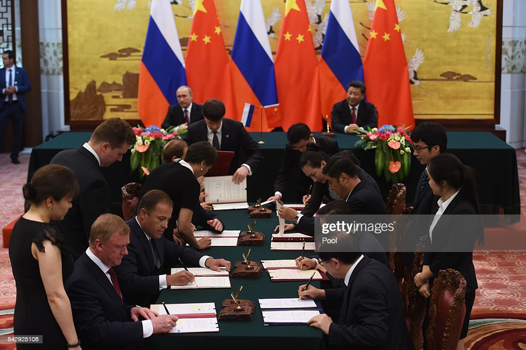 Officials sign documents as Russian President Vladimir Putin (back L) and Chinese President Xi Jinpin (back R) look on during a signing ceremony in Beijing's Great Hall of the People on June 25, 2016 in Beijing, China. Russian President Vladimir Putin is in China to discuss more economic and military cooperation between the two countries.