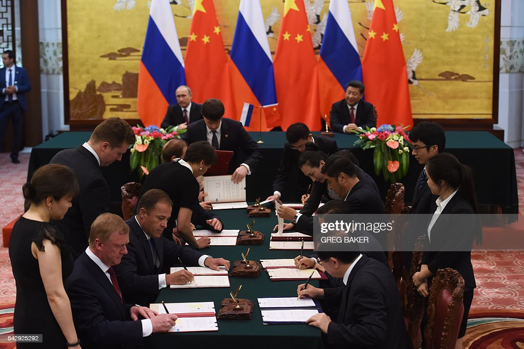 Officials sign documents as Russian President Vladimir Putin (back L) and Chinese President Xi Jinping (back R) look on during a signing ceremony in Beijing's Great Hall of the People on June 25, 2016. / AFP / POOL / GREG