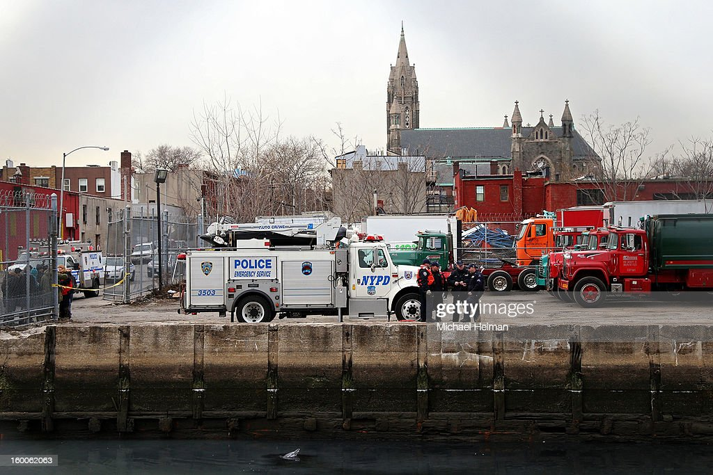 Officials stand on the side of the Gowanus Canal as a common dolphin comes up for air after getting stuck on January 25, 2013 in Brooklyn borough of New York City. Officials are waiting till high tide in the hopes that the stuck dolphin will be able to free itself from the canal.