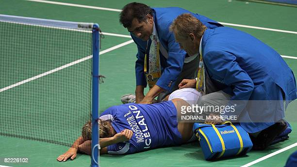 Officials talk to Raggna Bjorg Ingolfsdottir of Iceland after she suffered an injury while playing against Eriko Hirose of Japan during their women's...
