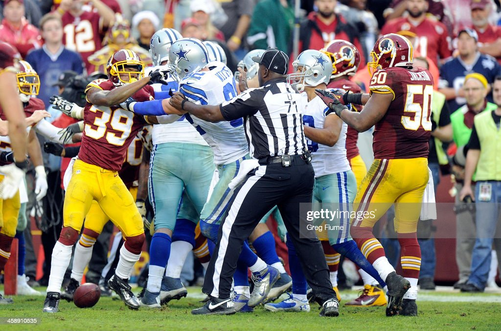 Officials try to break up an altercation in the fourth quarter between the Dallas Cowboys and the Washington Redskins at FedExField on December 22, 2013 in Landover, Maryland.