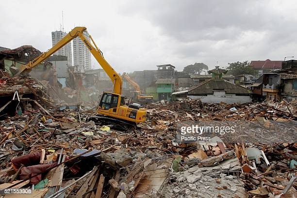 Officials use a bulldozer to demolish buildings at Kalijodo redlight district Bulldozers started demolishing hundreds of buildings in the Indonesian...