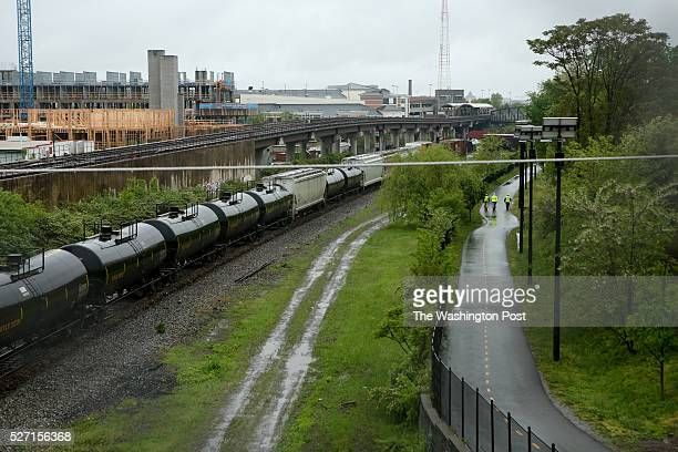 Officials walk on the Metropolitan Branch Trail closed to the public as they survey the scene of a CSX train derailment near the Rhode Island Ave...