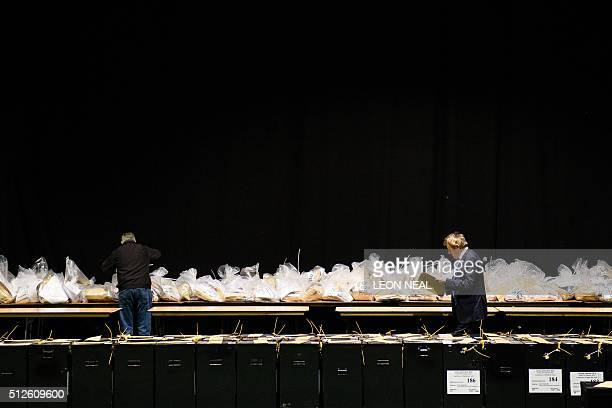 Officials walk past sealed ballot boxes as the count gets under way at the RDS centre in Dublin Ireland on February 27 2016 the day after the vote...