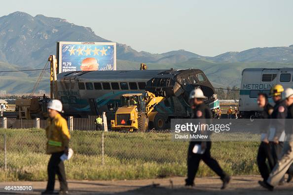 Officials walk to give a press conference as workers lift a rail car back onto the tracks after a Los Angelesbound Metrolink train derailed in a...