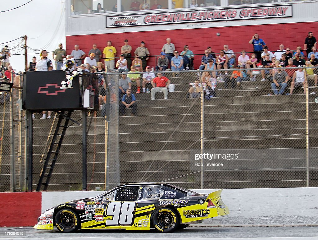 NASCAR officials wave the checkered flag as Dylan Kwasniewski passes the finish line at Greenville Pickens Speedway on September 2, 2013 in Greenville, South Carolina.