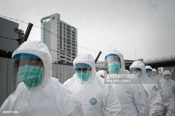 Officials wearing masks and protective suits proceed to cull chickens in Hong Kong on January 28 as Hong Kong began a mass cull of 20000 chickens...