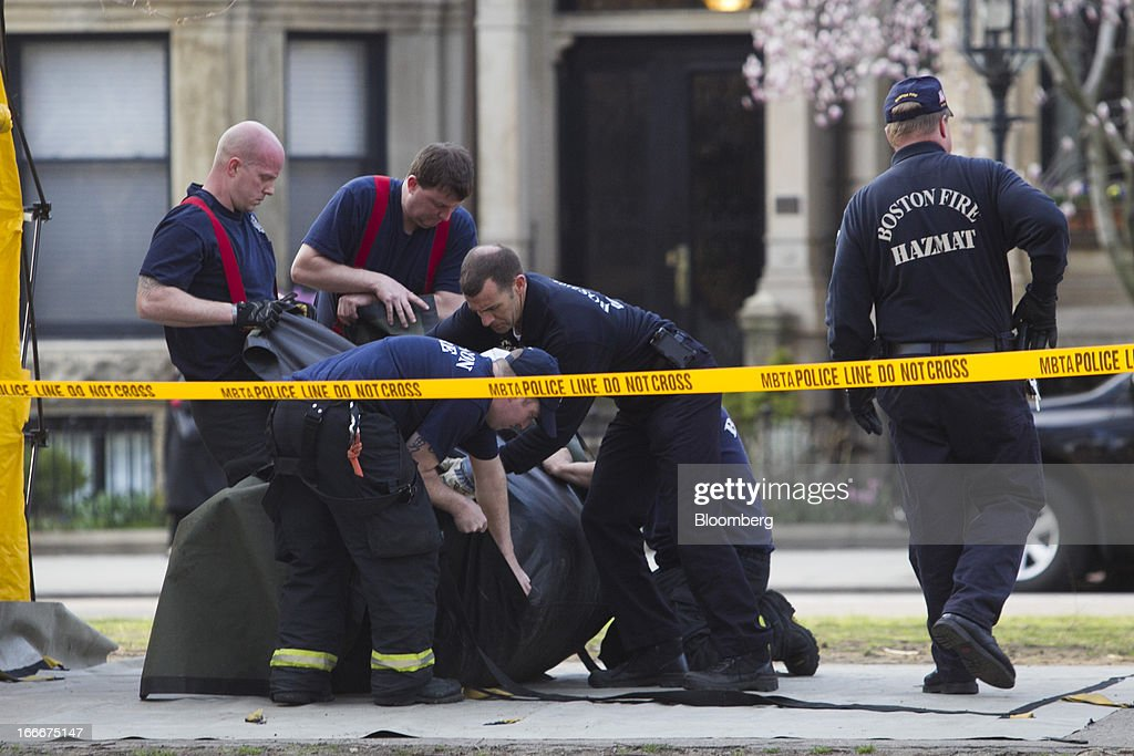 Officials with the Boston Fire Department Hazardous Materials (Hazmat) Unit wrap up a garbage can along Commonwealth Avenue after two explosions occurred along the final stretch of the Boston Marathon on Boylston Street in Boston, Massachusetts, U.S., on Monday, April 15, 2013. Powerful bombs killed two people and injured scores near the finish of the Boston Marathon, turning one of the world's oldest road races into bloody chaos. Photographer: Kelvin Ma/Bloomberg via Getty Images