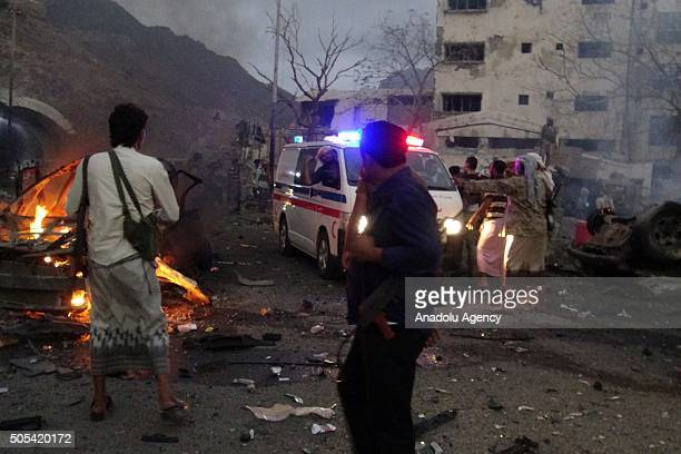 Officials work at the site of a bomb attack killing 11 people outside the house of the Aden police chief Chalal Hadi in Aden Yemen on January 17 2016