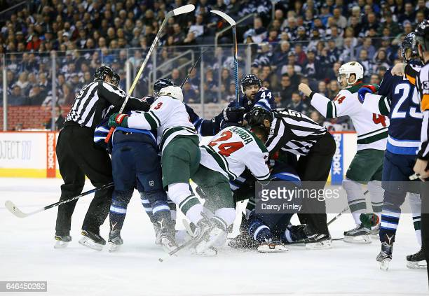 Officials work to separate Winnipeg Jets and Minnesota Wild players during a first period scrum at the MTS Centre on February 28 2017 in Winnipeg...