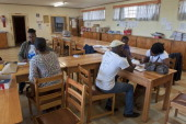 Officials working for the Independant Electoral Commission help applicants on the second day of voter registration at a voting station in a school in...