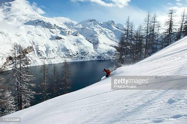 Offpiste skier enjoys the fresh powder snow that has fallen in the backcountry Tignes FRANCE