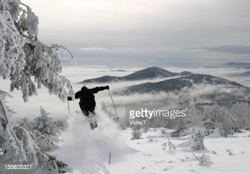 Off-piste skier jumping a bump