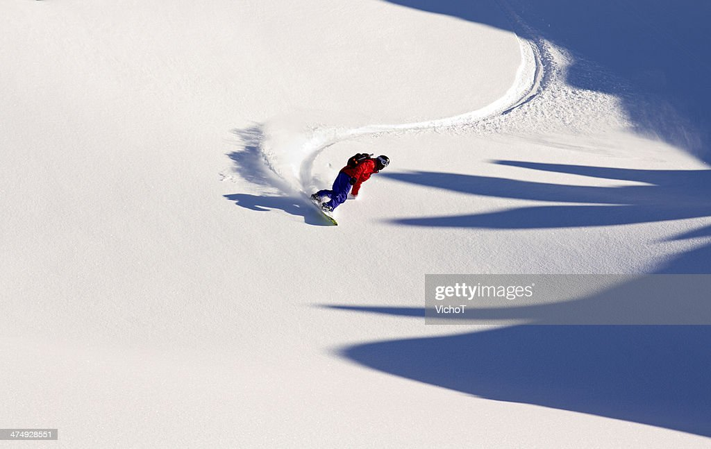 Off-piste snowboarder having fun in the powder