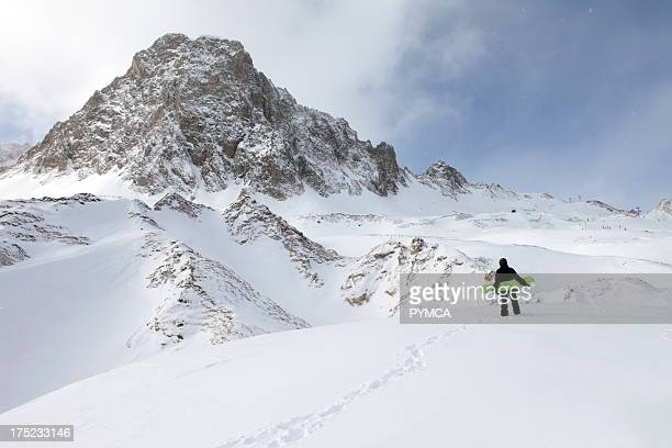 Offpiste snowboarder sets off on foot to hike to an area of untracked fresh powder snow that has fallen in the backcountry Tignes FRANCE