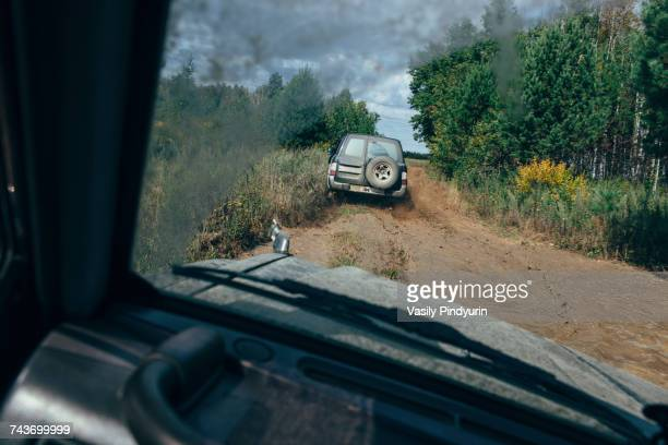 Off-road vehicle moving on dirt road amidst trees seen through windshield against sky