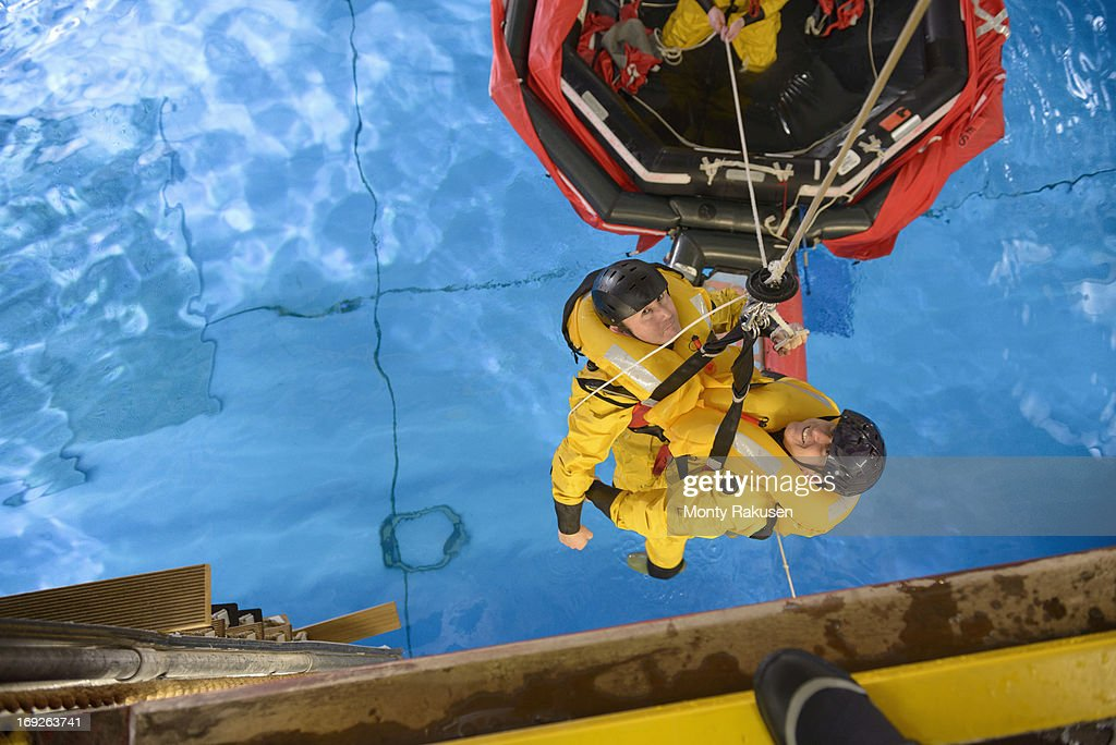 Offshore oil workers hoisted from raft in sea ditching survival training in pool facility