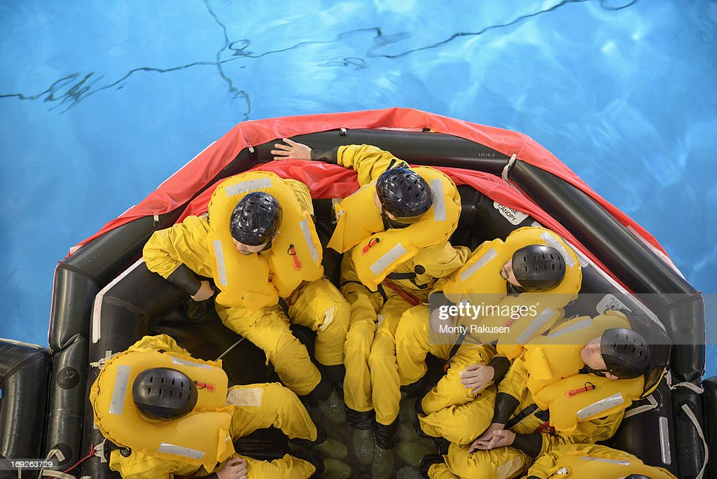 Offshore oil workers in raft being trained in sea ditching survival in pool facility, overhead view