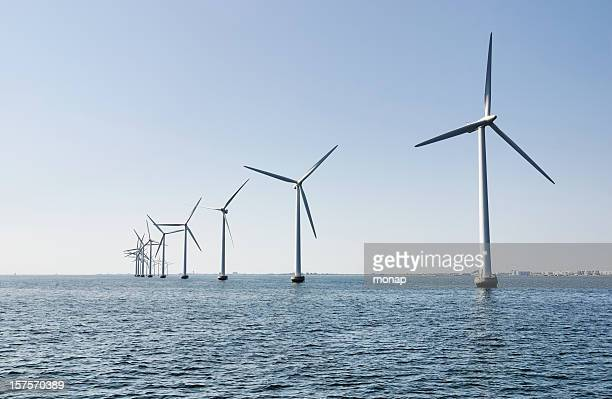 Offshore wind turbines, industrial area in the horizon