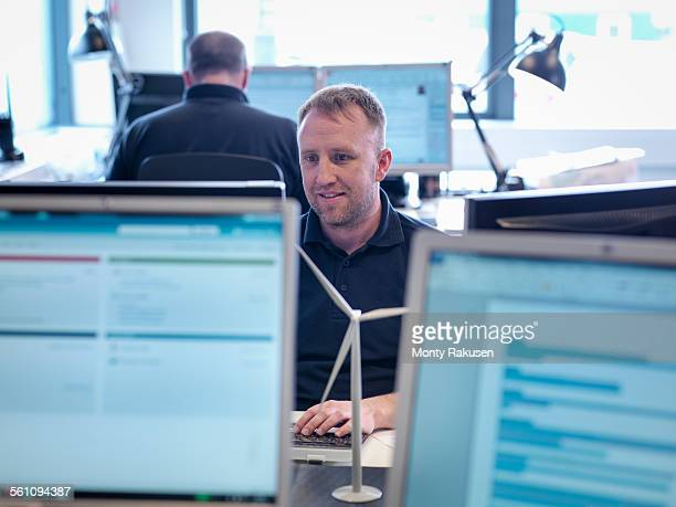 Offshore windfarm engineer working with computer screens in office