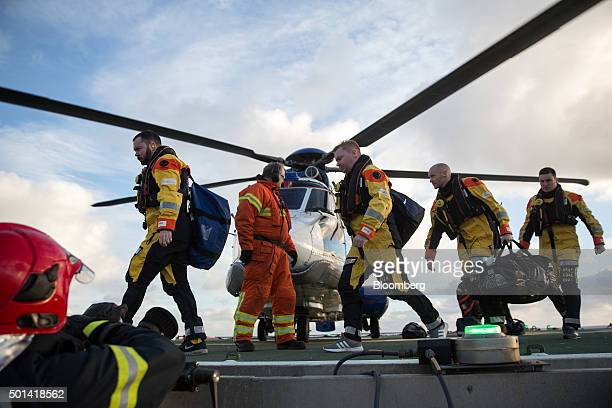 Offshore workers exit a Bristow AS332 Super Puma helicopter as they arrive on the Armada gas condensate platform operated by BG Group Plc in the...