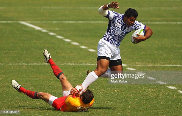 Ofisa Treviranus of Samoa is tackled by Ben Gollings of England during the rugby 7's quarter final match between England and Samoa at Delhi...