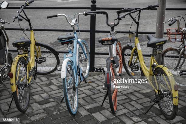 Ofo Inc left and right Xiaoming Danche second left and Mobike second right bicycles stand parked next to each other on a sidewalk in Shanghai China...
