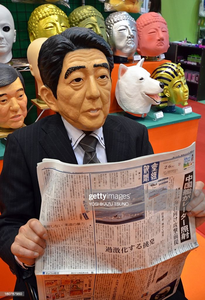 Ogawa Rubber, Japan's top rubber mask maker employee, wearing a rubber mask of Japanese Prime Minister Shinzo Abe, reads a newspaper reporting Chinese frigate locked on fire-control rader on a Japanese warship at the Tokyo International Gift Show in Tokyo on February 6, 2013. The hawkish prime minister described the radar-locking as 'unilateral provocative action by the Chinese side' at the parliament session. AFP PHOTO / Yoshikazu TSUNO