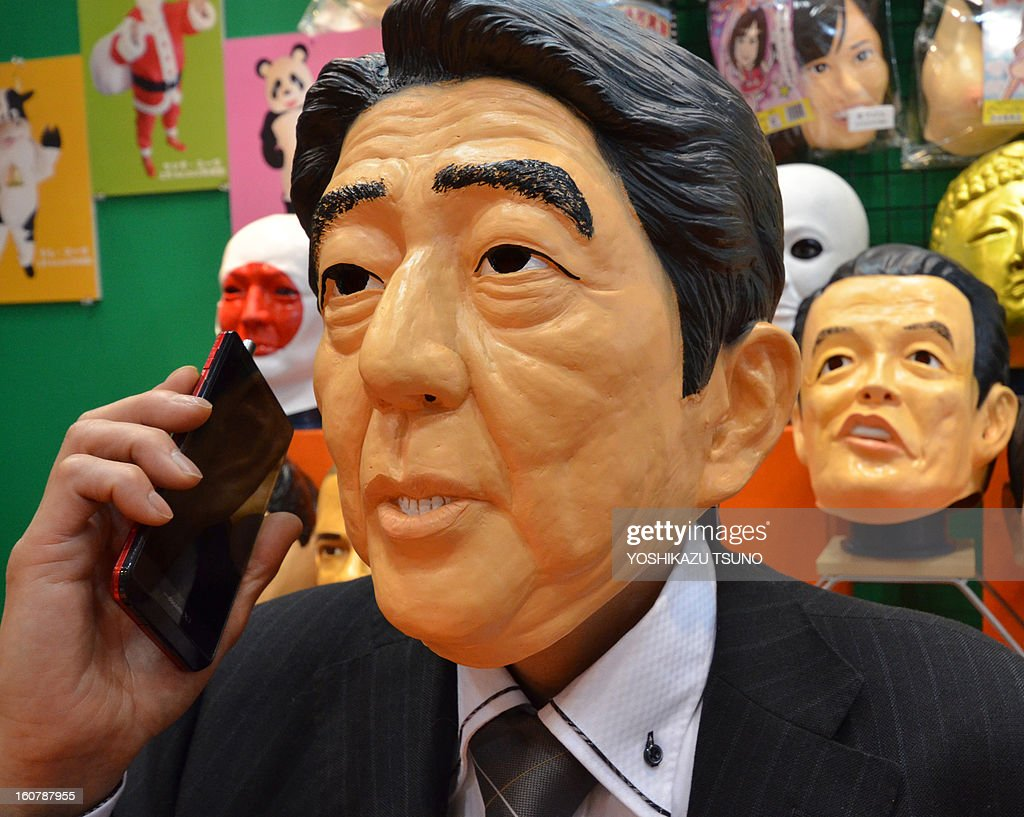 Ogawa Rubber, Japan's top rubber mask maker employee, wearing a rubber mask of Japanese Prime Minister Shinzo Abe, uses his mobile phone at the Tokyo International Gift Show in Tokyo on February 6, 2013. The hawkish prime minister described the radar-locking as 'unilateral provocative action by the Chinese side' at the parliament session. AFP PHOTO / Yoshikazu TSUNO
