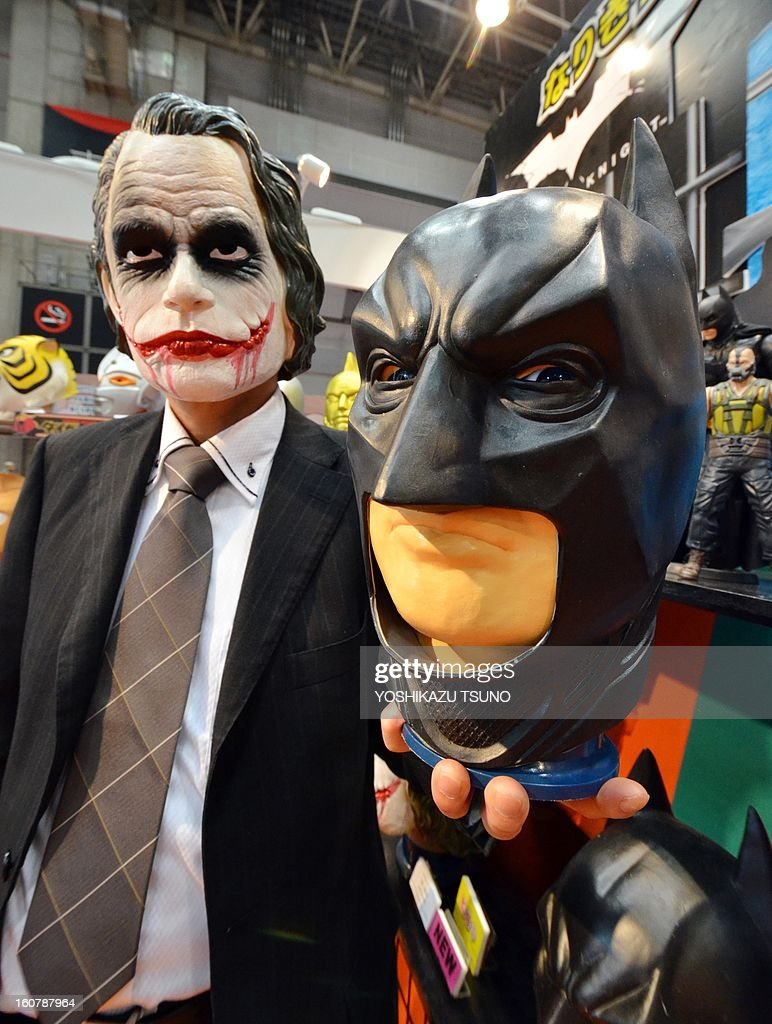 Ogawa Rubber, Japan's top rubber mask maker employee, wearing a rubber mask of Joker, shows a mask of Batman at the Tokyo International Gift Show in Tokyo on February 6, 2013. The masks will go on sale here soon. AFP PHOTO / Yoshikazu TSUNO