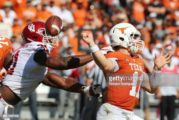 Ogbonnia Okoronkwo of the Oklahoma Sooners forces a fumble by Sam Ehlinger of the Texas Longhorns in the first quarter at Cotton Bowl on October 14...