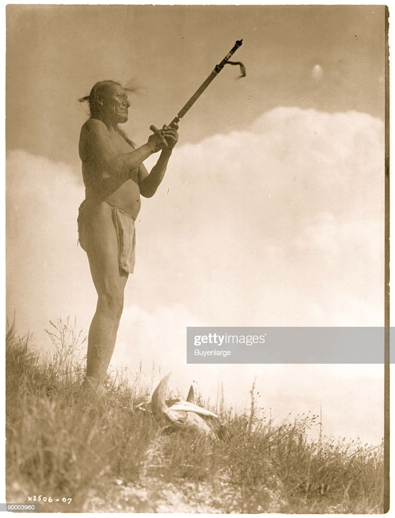 Oglala Sioux man Picket Pin wearing breechcloth holding pipe with mouthpiece pointing skyward buffalo skull at his feet
