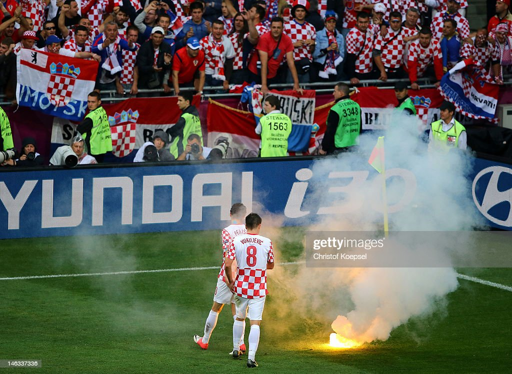 Ognjen Vukojevic and Ivan Perisic of Croatia look at flare that has been thrown onto the pitch during the UEFA EURO 2012 group C match between Italy and Croatia at The Municipal Stadium on June 14, 2012 in Poznan, Poland.