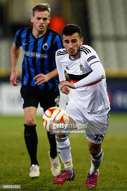 Oguzhan Ozyakup of Besiktas gets past Laurens De Bock of Brugge during the UEFA Europa League Round of 16 1st leg match between Club Brugge KV and...