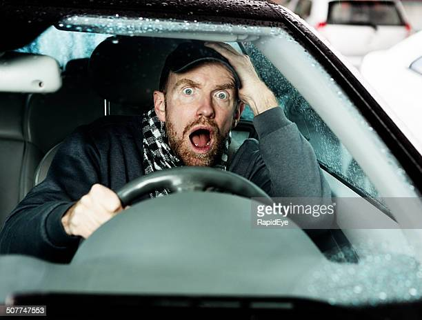 Oh no! Horrified male driver gasping, hand to head