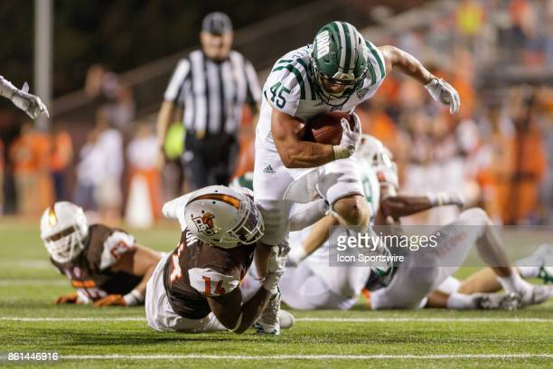 Ohio Bobcats running back AJ Ouellette rushes the ball while Bowling Green Falcons defensive back Marcus Milton tries to complete a tackle in the...