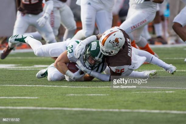 Ohio Bobcats running back David Burroughs is tacked by Bowling Green Falcons defensive end Nilijah Ballew during game action between the Ohio Bobcats...