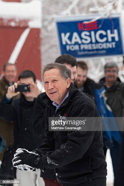 Ohio Governor and Republican presidential candidate John Kasich smiles during a snowball fight with his staff following a town hall style meeting on...