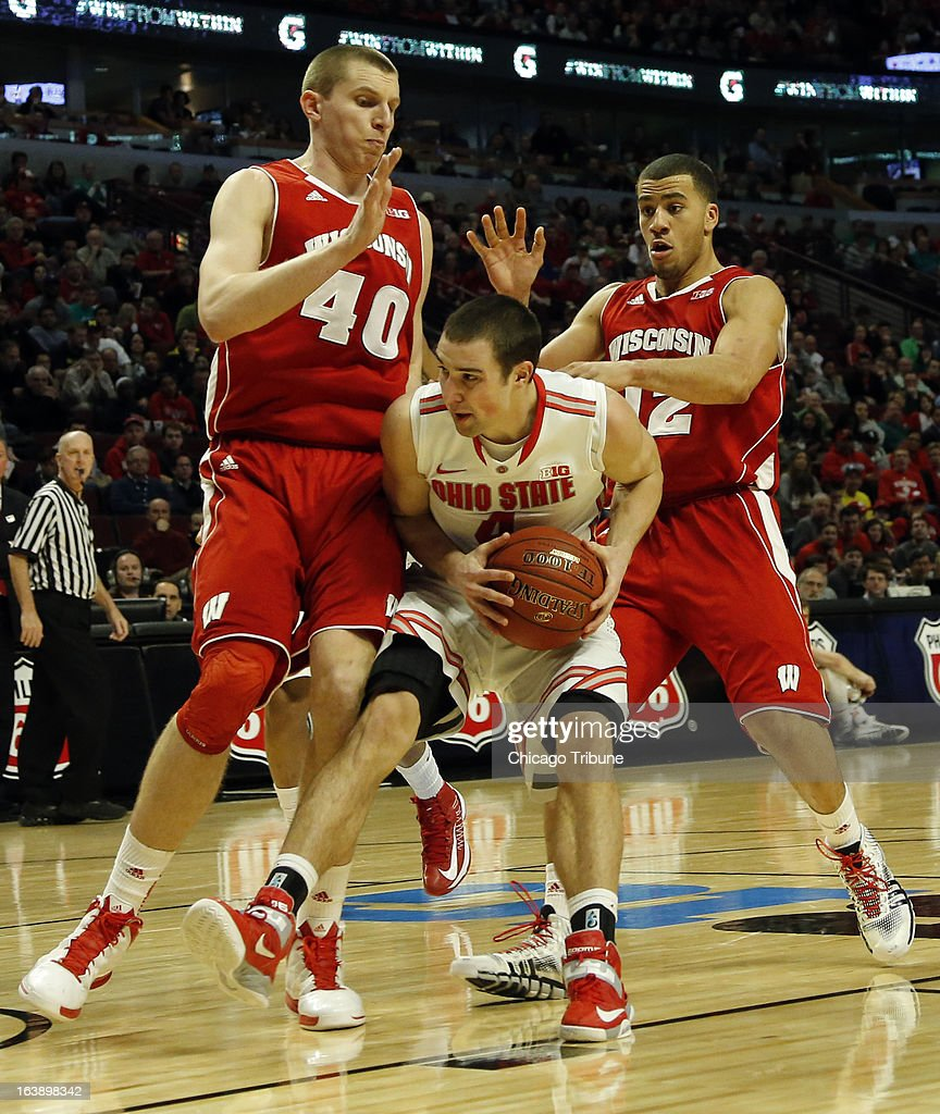 Ohio State Buckeyes guard Aaron Craft (4) drives to the basket against Wisconsin Badgers forward/center Jared Berggren (40) and Wisconsin Badgers guard Traevon Jackson (12) during the second half in the finals of the men's Big Ten basketball tournament at the United Center in Chicago, Illinois, Sunday, March 17, 2013. Buckeyes win, 50-43.