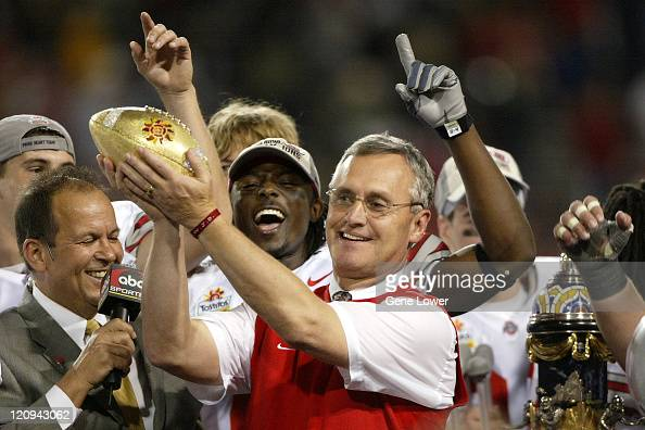 Ohio State Buckeyes head coach Jim Tressel raises the trophy after the Fiesta Bowl game against the Notre Dame Fighting Irish at Sun Devil Stadium in...
