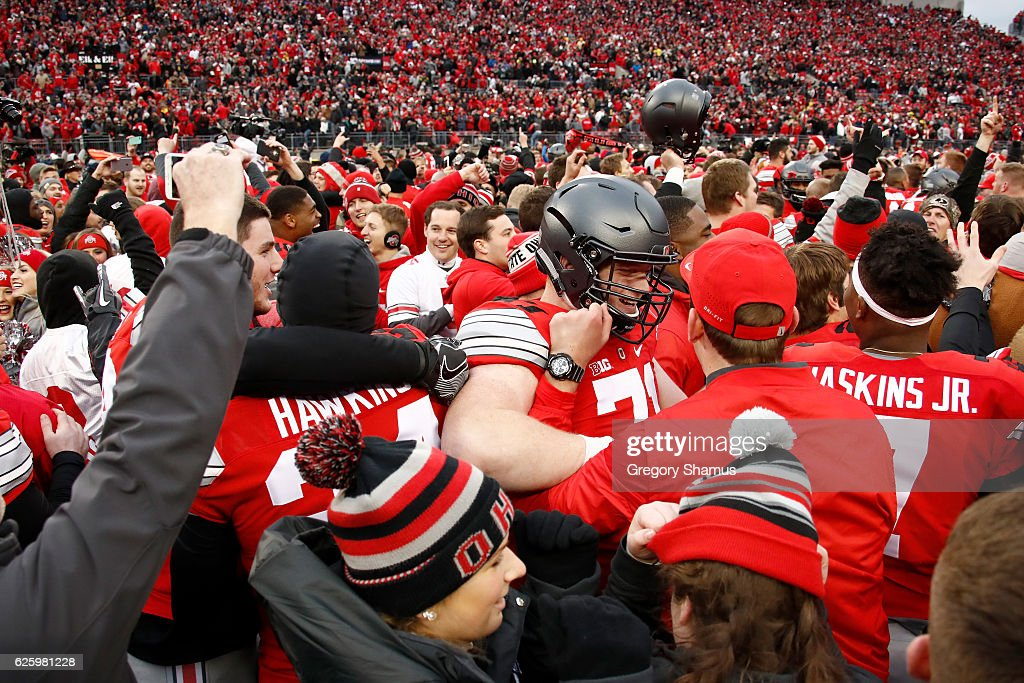 Ohio State Buckeyes players and fans celebrate on the field after their double-overtime victory over the Michigan Wolverines at Ohio Stadium on November 26, 2016 in Columbus, Ohio.