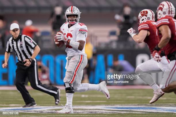 Ohio State Buckeyes quarterback JT Barrett scrambles to the outside while looking downfield during the Big 10 Championship game between the Wisconsin...