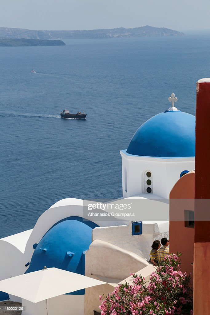 Oia church with cupola painted blue and white washed walls with wonderful views to the sea caldera and volcano on June 30 2015 in Santorini Greece...