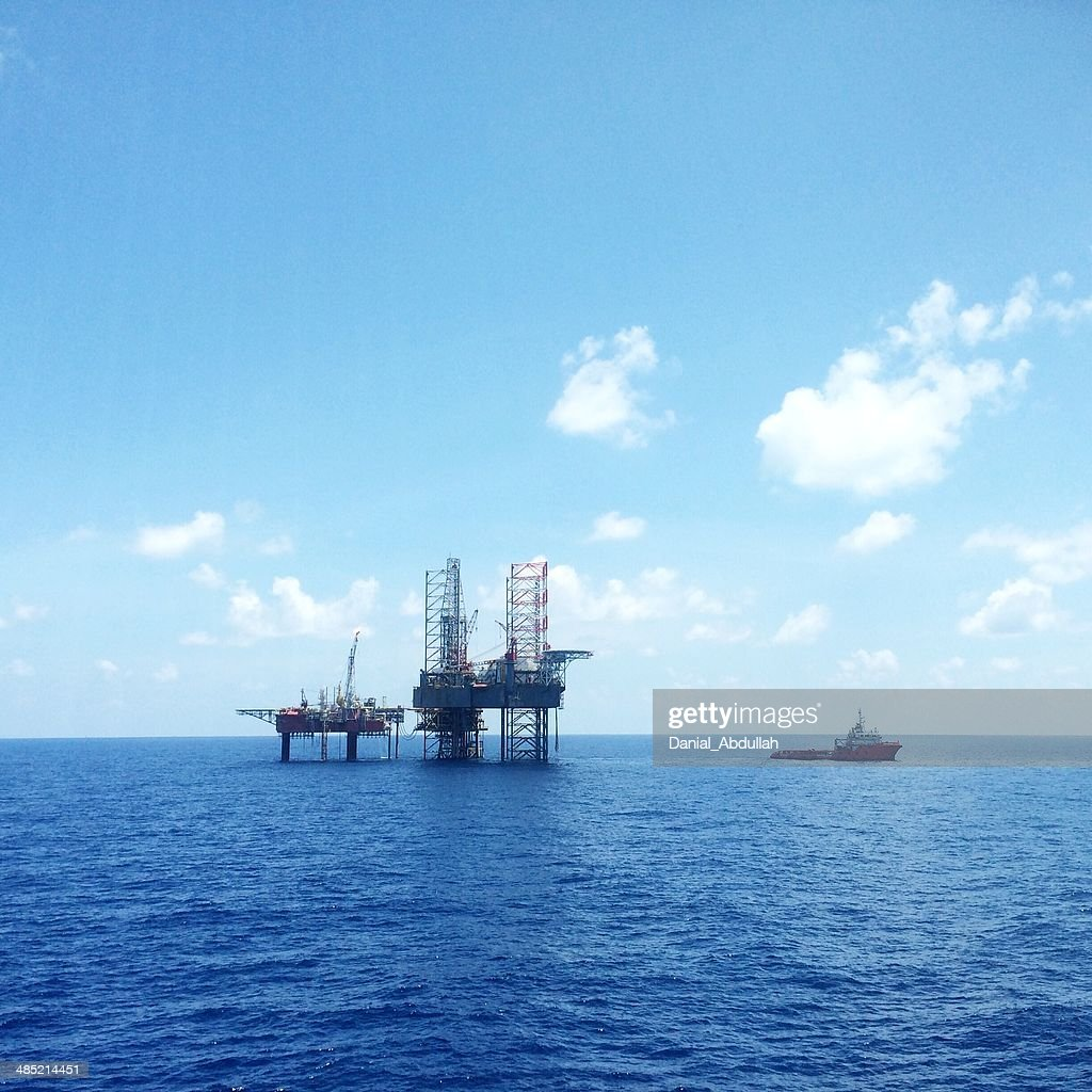 Oil and gas platform with offshore vessel transporting cargo : Stock Photo