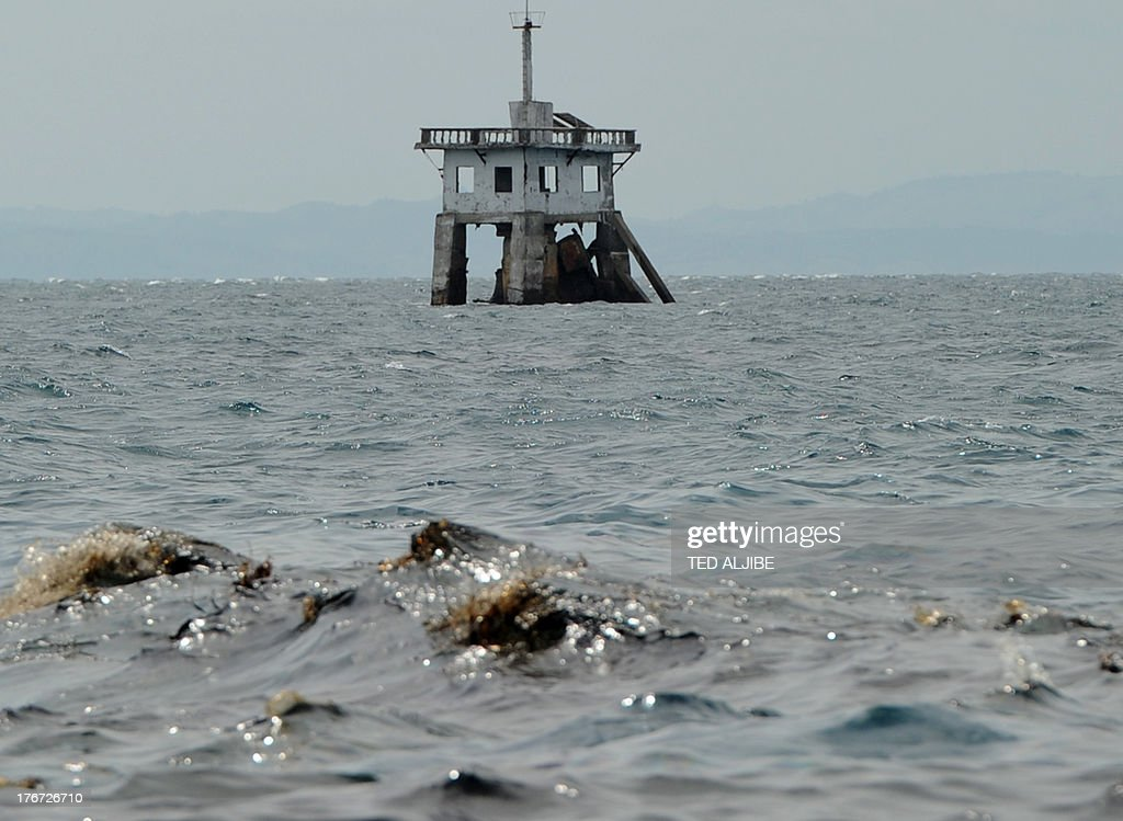 Oil (foreground) believed to be from a sunken ferry floats on the waters surface in Talisay town near Cebu City, central Philippines on August 18, 2013, two days after a ferry and a freighter collided. Philippine rescuers struggled in rough seas August 18, as they resumed a bleak search for 85 people missing in the country's latest ferry disaster, but insisted miracle survivor stories were possible. AFP PHOTO/TED ALJIBE