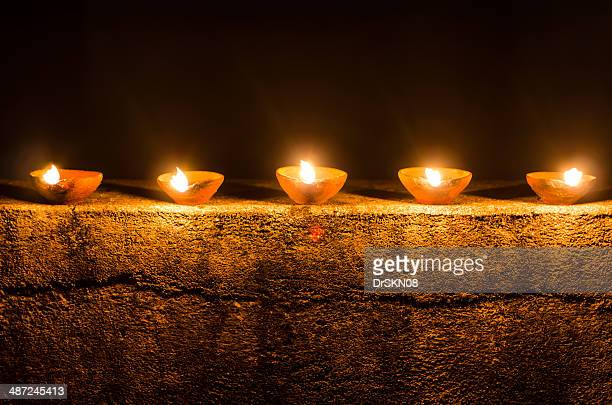 Oil candles decoration on old wall in Diwali