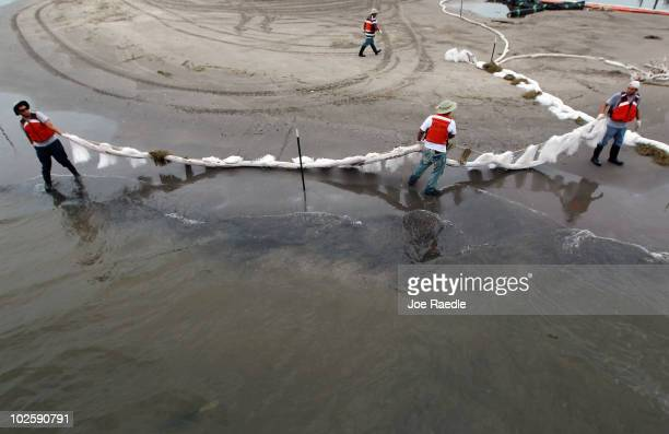 Oil cleanup workers place absorbent material along the waters edge as they try to keep the residue from the Deepwater Horizon oil spill in the Gulf...