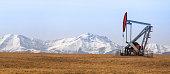 Oil 'donkey' pumps on grass slope below snowy mtns
