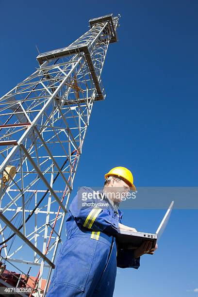 Oil Engineer using a Computer at an Oil Rig